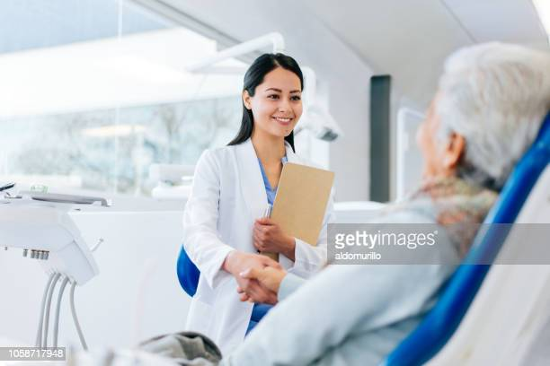 latin female doctor and patient greeting with handshake - dentist stock pictures, royalty-free photos & images