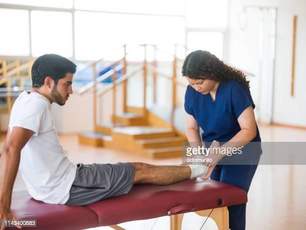 enfermeira fêmea latin que põr uma atadura em torno do tornozelo do paciente - bandagem - fotografias e filmes do acervo