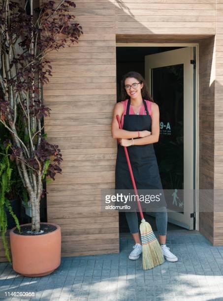 ドアにほうきで立っているラテン女性の店員 - 掃く ストックフォトと画像