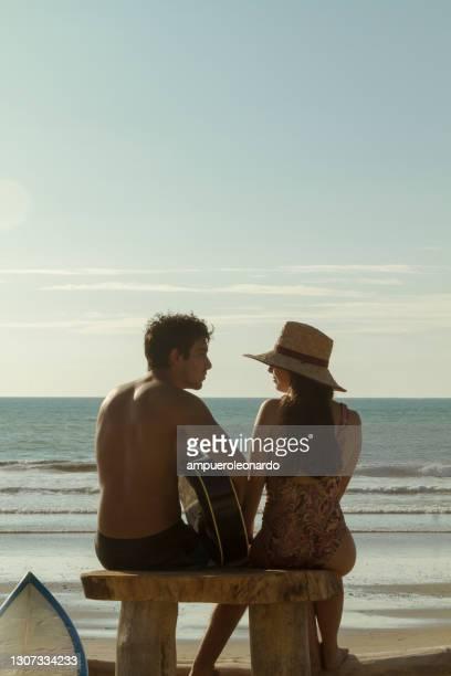 un couple hétérosexuel latin de surfer de muscle d'ajustement, jouant une guitare acoustique devant l'océan, détendant à canoa, province de manabi, equateur, amérique latine - petit ami photos et images de collection
