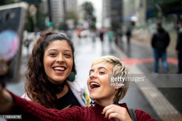 lateinische freunde, die ein selfie im freien machen - websurfen stock-fotos und bilder