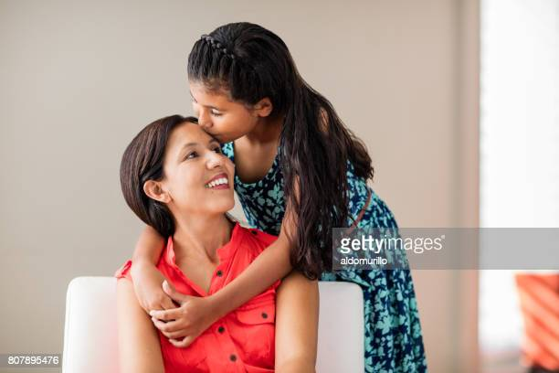 latin girl embracing and kissing mother on forehead - mexican mom stock photos and pictures