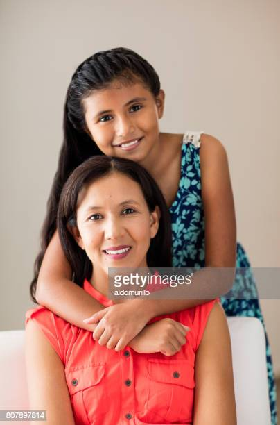 Latin girl embracing mother from behind and smiling at camera