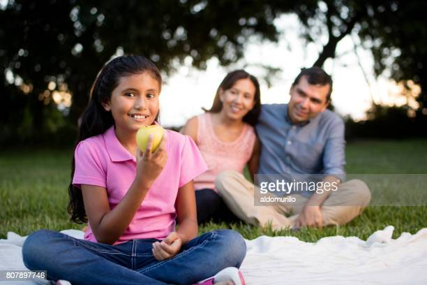 Latin girl holding apple and smiling at camera