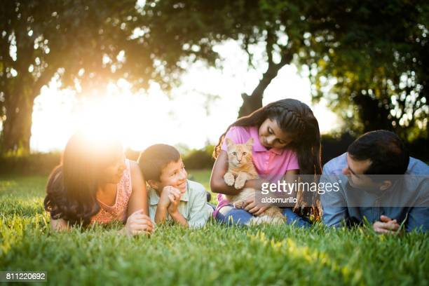 Latin girl holding cat and sitting with her family
