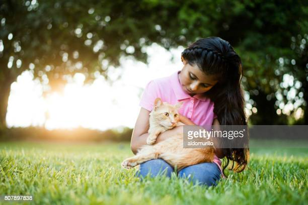 Latin girl sitting with cat and caressing it