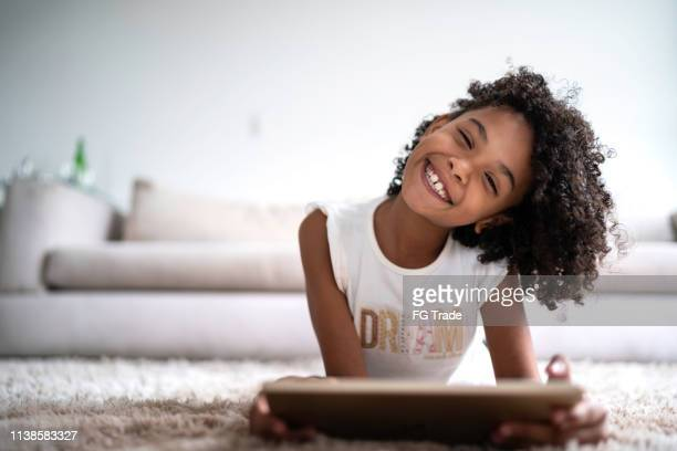 menina latin que usa a tabuleta digital em casa-retrato - criança - fotografias e filmes do acervo