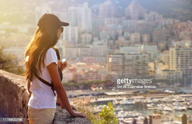 latin girl with cap and sunglasses enjoying beautiful views under the sunset sunlight - monte carlo stock pictures, royalty-free photos & images