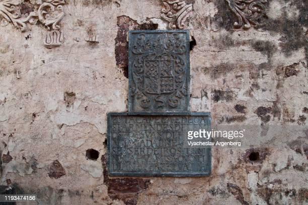 latin inscriptions in the church of st. augustine, old goa, india - argenberg stock-fotos und bilder