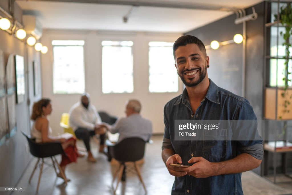 Retrato masculino Latin usando o móbil no estúdio do trabalho : Foto de stock