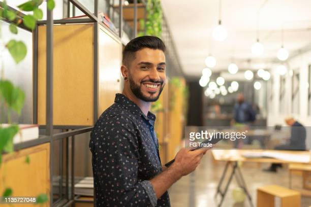 latin male portrait using tablet at work studio - brazilian ethnicity stock pictures, royalty-free photos & images