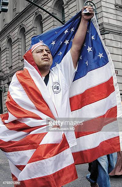 Latin man draped in AMERICAN FLAG at a pro immigration ralley in MANHATTAN NYC