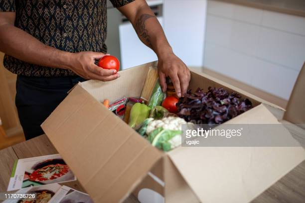 latin man opening parcel with meal kit - meal stock pictures, royalty-free photos & images