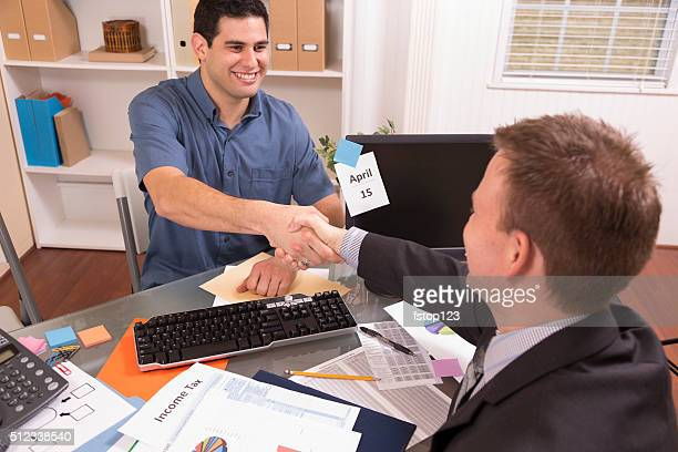Latin man reviews financial tax documents with accountant. Office.