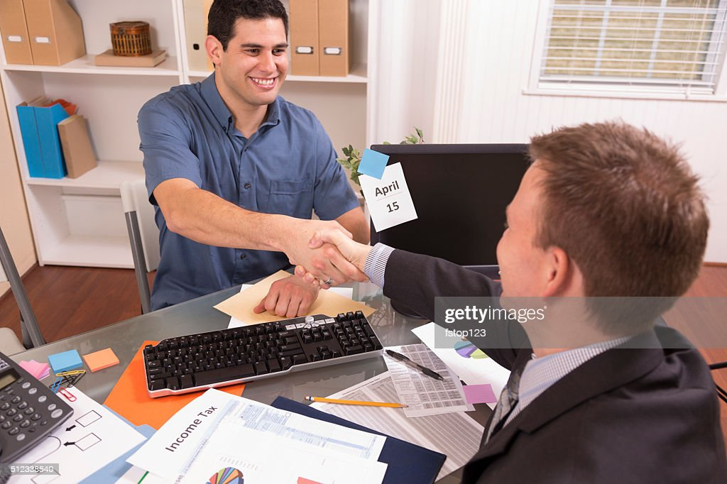 Latin Man Reviews Financial Tax Documents With Accountant Office Stock  Photo | Getty Images