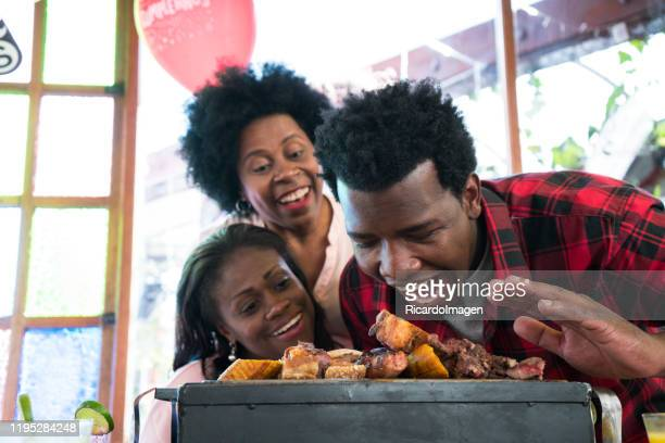 latin man with afro hair and brown skin, approximately 29 years old, has a barbecue with meat of chorizo sausage in front of him, looks at the camera and opens his big mouth while we look back at his wife and mother-in-law watching him - 25 29 years stock pictures, royalty-free photos & images