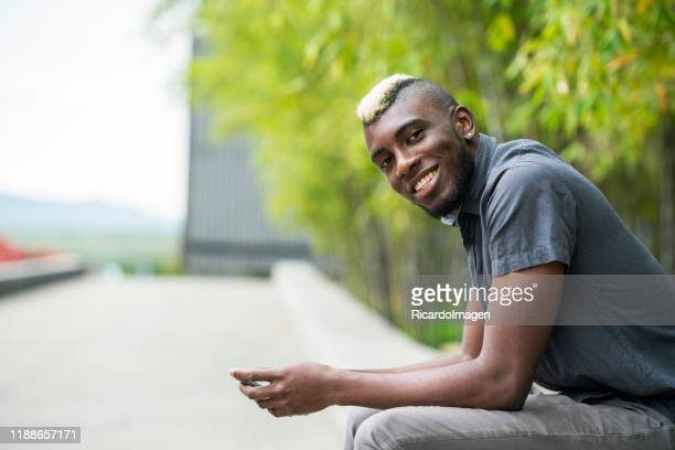 latin man with brown skin and yellow hair dressed casually chatting on cell phone - 25 29 anos imagens e fotografias de stock