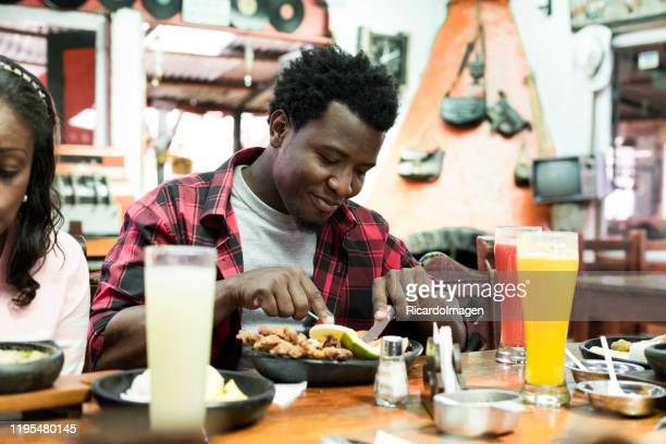 latin man with dark skin and afro hair of approximately 29 years old is sitting at the wooden table of a beautiful restaurant of typical colombian food eating his delicious favorite dish with a big sorisa on his face - 25 29 years stock pictures, royalty-free photos & images