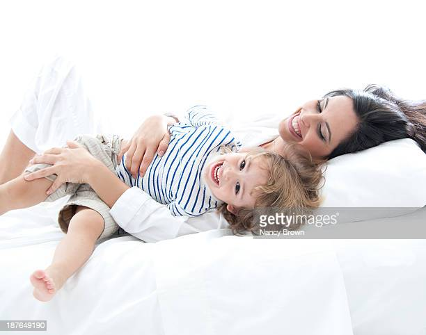 Latin Mom and Son Playing in Bed.