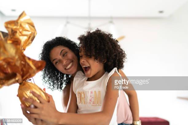 latin mother and daughter celebrating easter at home - easter imagens e fotografias de stock