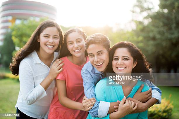 Latin mother and teenage children smiling at camera