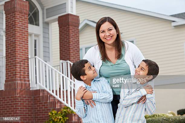 Latin mother and twin boys outside townhouse