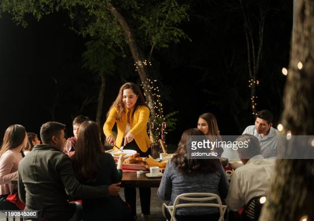latin mother standing and serving food at table with family - serving food and drinks stock pictures, royalty-free photos & images