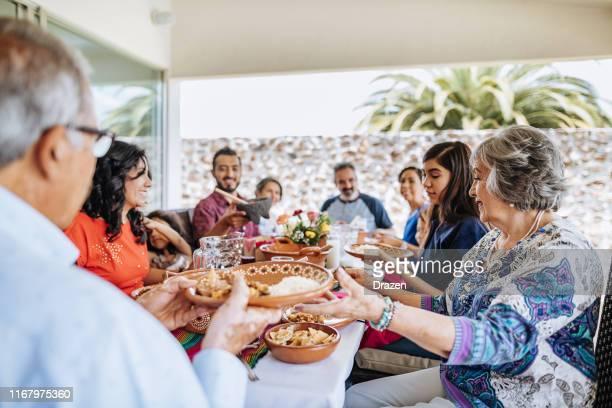 latin multi-generatie familie die feest op zondagse lunch - nosotroscollection stockfoto's en -beelden