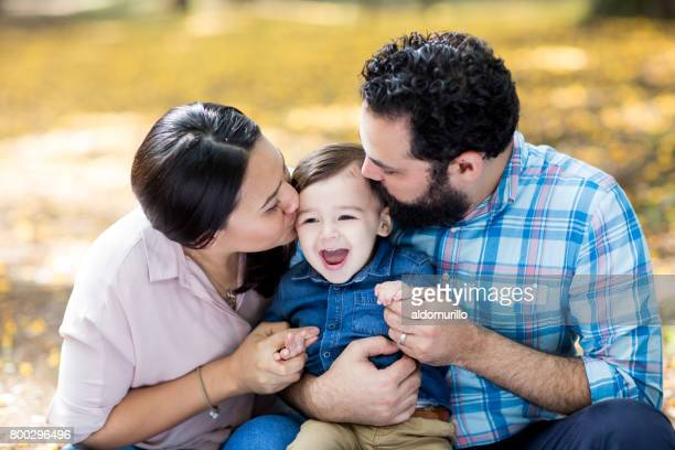 Latin parents holding and kissing little boy