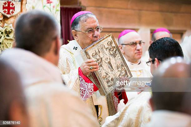 Latin Patriarch of Jerusalem Fouad Twal kisses the Book of the Gospels during the celebration of the Holy Thursday mass the Church of the Holy...