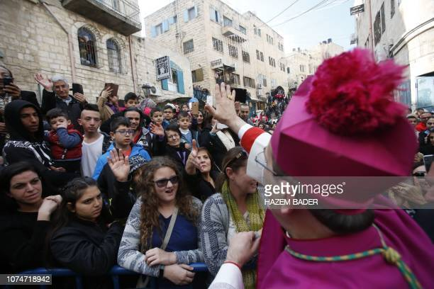 Latin Patriarch of Jerusalem Pierbattista Pizzaballa greets a crowd as he arrives in the West Bank city of Bethlehem, on December 24, 2018.