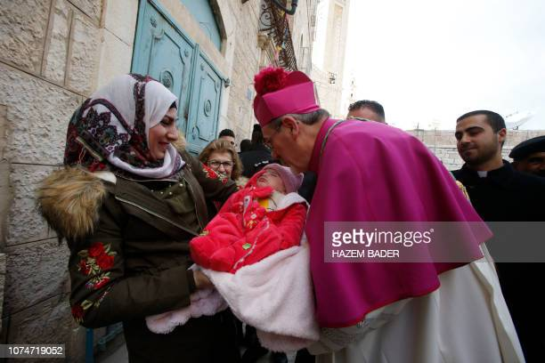 Latin Patriarch of Jerusalem Pierbattista Pizzaballa greets a Muslim Palestinian woman and a baby in the West Bank city of Bethlehem on December 24...
