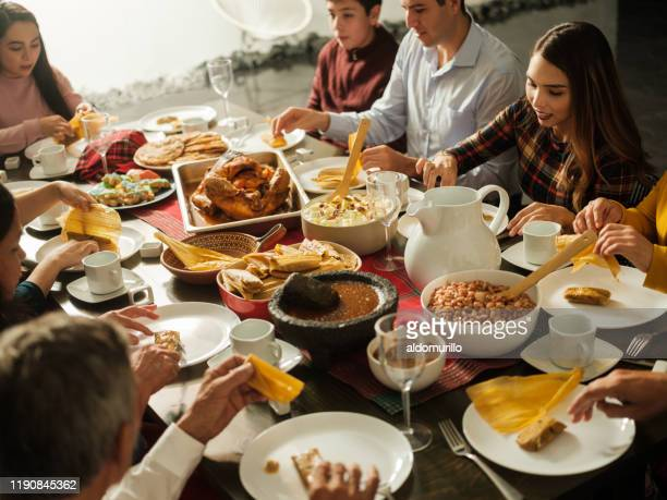 latin people eating traditional mexican food at table - mexican christmas stock photos and pictures