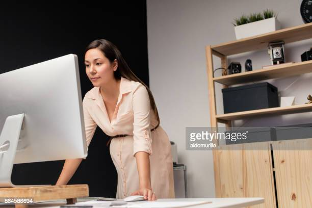 Latin pregnant woman working at the home office