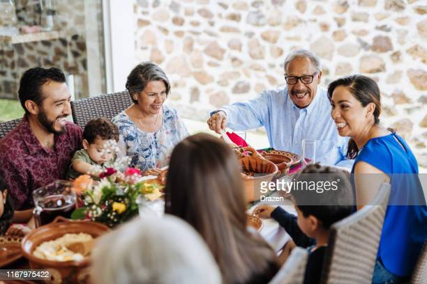 latin senior man serving the food to his family at dinner table - latin american and hispanic ethnicity stock pictures, royalty-free photos & images