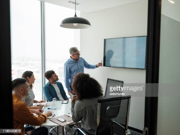 latin senior manager geeft presentatie op het scherm - kleine groep mensen stockfoto's en -beelden