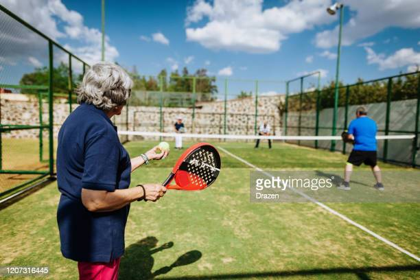 latin senior women playing paddle tennis outdoors in springtime - racket sport stock pictures, royalty-free photos & images