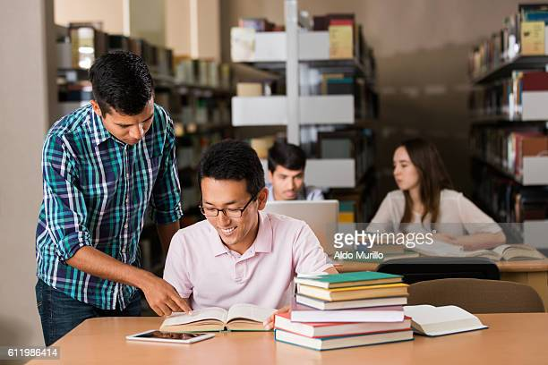 Latin student standing next asian student in the library