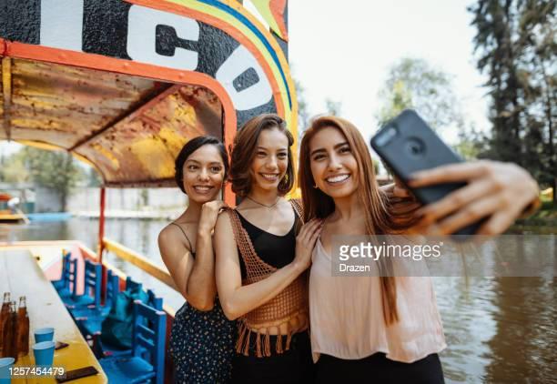 latin reisende auf städtereise genießen bootsfahrt - passagier wasserfahrzeug stock-fotos und bilder