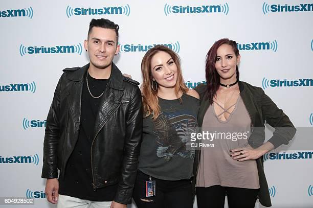 Latin urban duo Domino Saints poses with Marisol Vargas at SiriusXM Studios on September 13 2016 in New York City