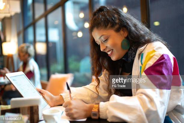latin woman analyzing some data from a digital investment using digital tablet, taking notes - financial technology stock pictures, royalty-free photos & images