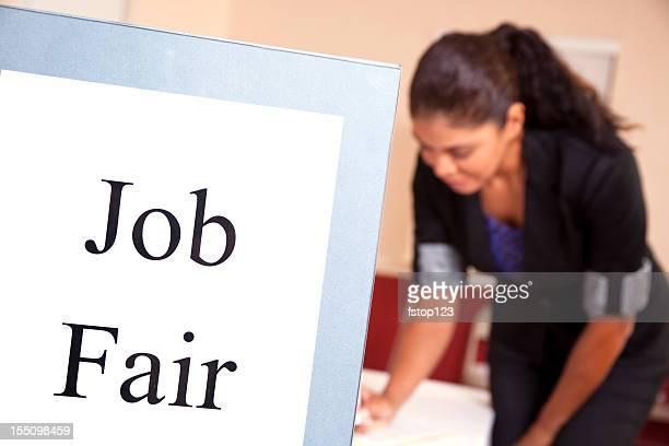 latin woman at job fair registration table. - job fair stock pictures, royalty-free photos & images