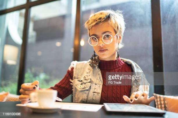 latin woman checking some graphics from digital investment - short hair stock pictures, royalty-free photos & images