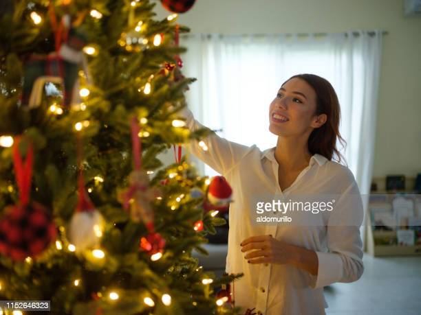 latin woman decorating a christmas tree - mexican christmas stock photos and pictures