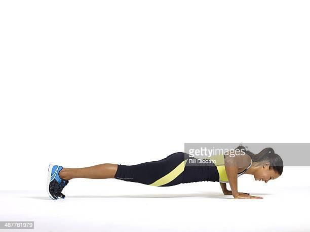 latin woman doing plank in studio
