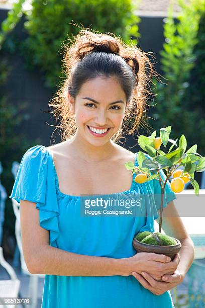 latin woman holding fruit tree - hair back stock pictures, royalty-free photos & images