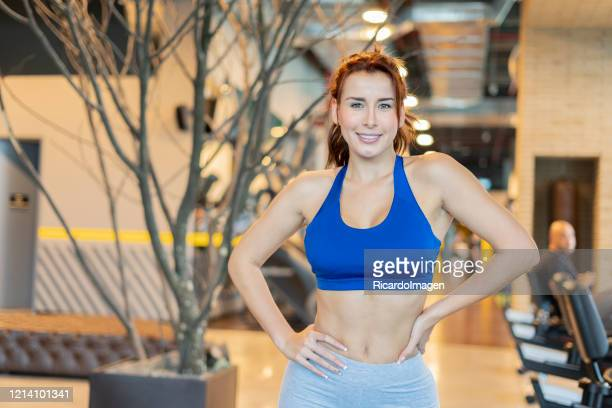latin woman in the gym looks at the camera - musculoso stock pictures, royalty-free photos & images