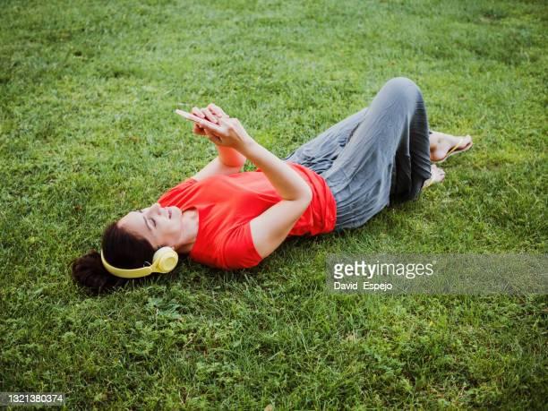 latin woman lying on the grass listening to music - tranquil scene imagens e fotografias de stock