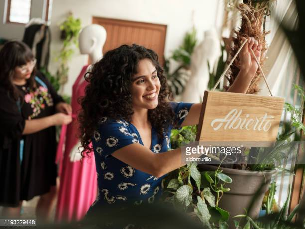 latin woman putting open sign in clothes shop - store opening stock pictures, royalty-free photos & images