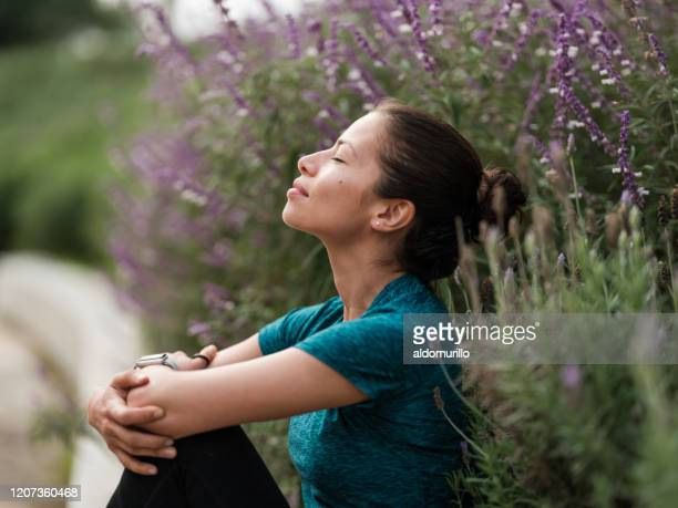 latin woman relaxing next to flowers - inhaling stock pictures, royalty-free photos & images